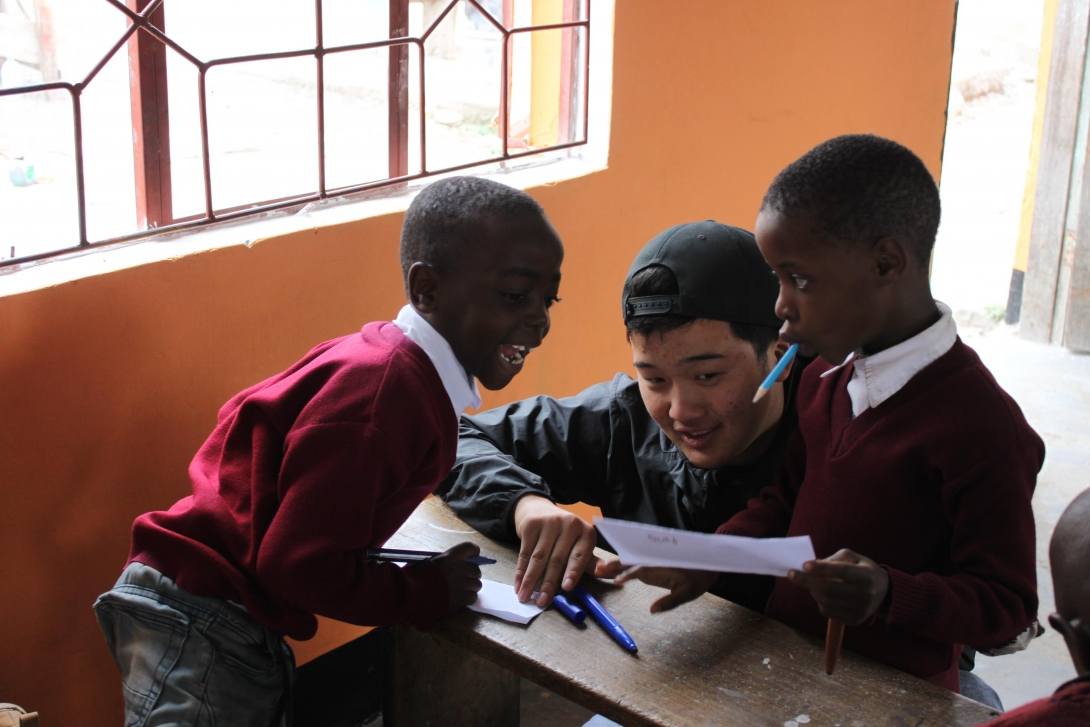 A high school students helping two children with basic English during his volunteering abroad trip